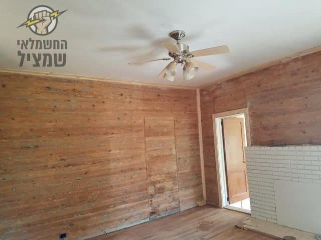 חשמלאי באשקלון מתקין מאוורר תקרה בחדר בבית מעץ