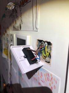 חשמלאי באשדוד בודק קצר בשקע בקיר בדירה ברובע ט בעיר