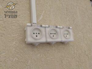 יצירת נקודת חשמל עם כמה יציאות בהתקנה של תעלות פלסטיק על הקיר
