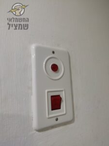חשמלאי מתקין מתג לדוד שמש בתוך הקיר בדירה באזור