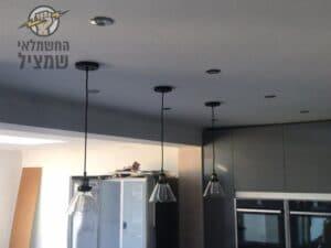 חשמלאי מתקין גופי תאורה נופלים במטבח בבית פרטי ביהוד